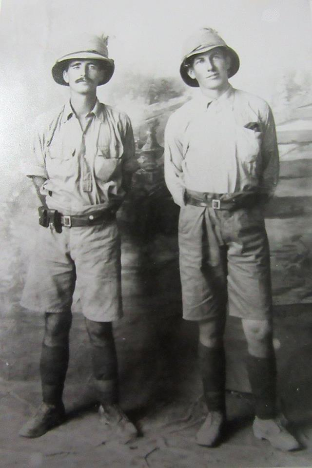 Black and White photo of Fred Morey and John Gordon Leslie (Gordon) Campbell taken in the Middle East during World War I.  They both wear pith helmets, light coloured shirts, and knee-length shorts with leggings and boots.  The picture is taken in a Studio in front of a painted backdrop.