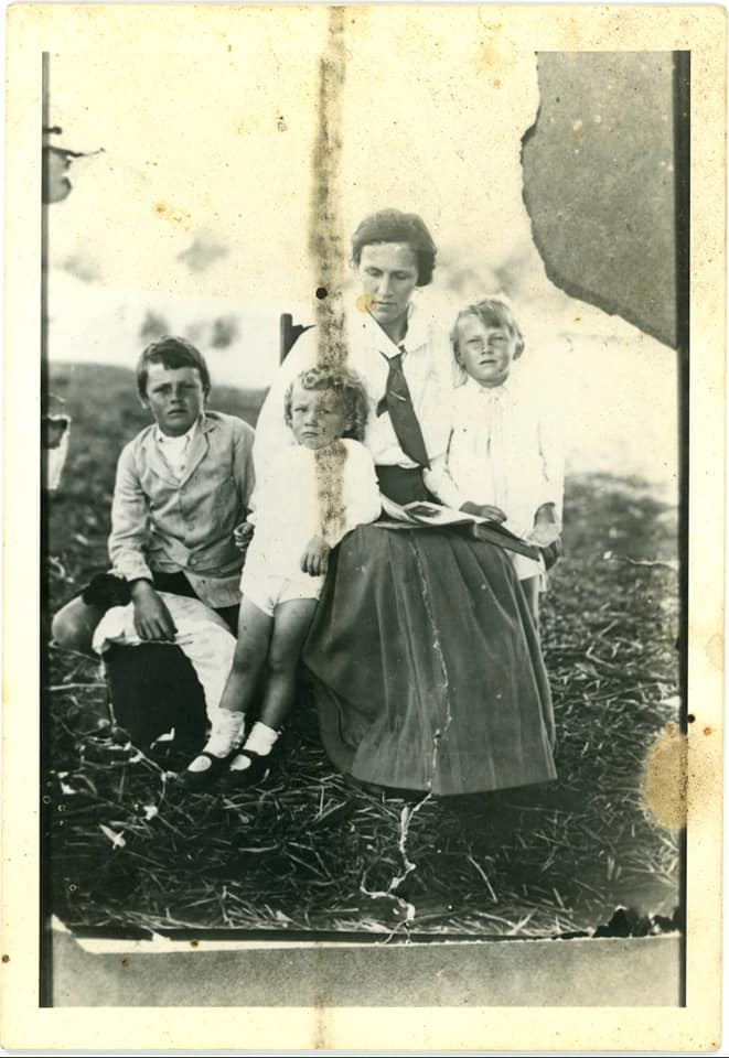 Black and white photograph of Gladys Campbell and sons Vivian, Colin & Leslie.  She is seated on a chair in the garden and appears to be reading the children a book.