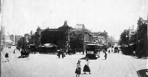 View of a historic street scene on the corner of two busy streets in early 1900s Brisbane