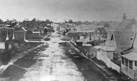 View of Adelaide Street, Brisbane taken in 1860 showing a dirt street and wooden houses