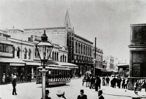 The corner of Queen and Goerge Streets showing many people out walking the streets in period dress