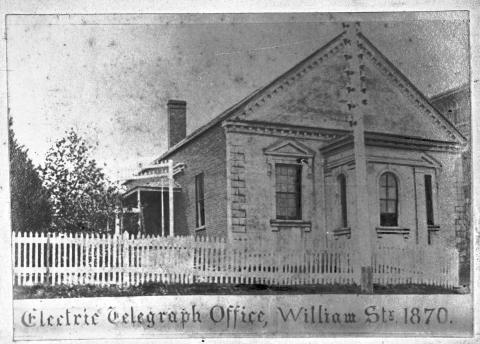 The Electric Telegraph Office brick building with white picket fence in front.