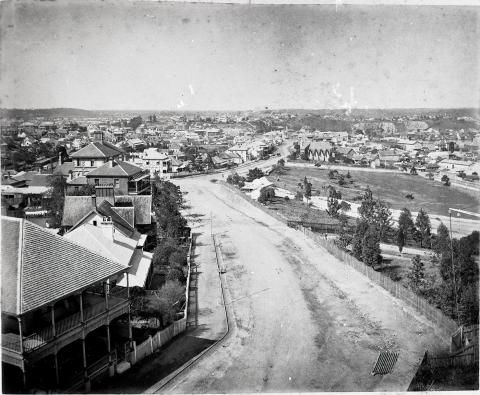 Sweeping view of Wickham Terrace showing a dirt road and numerous wooden houses