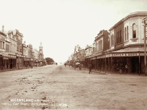 View of East Street, Rockhampton showing carts, horses and buildings.
