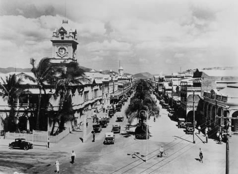 View of Townsville's Flinders Street with hundreds gathered for a street procession in the early 1930s