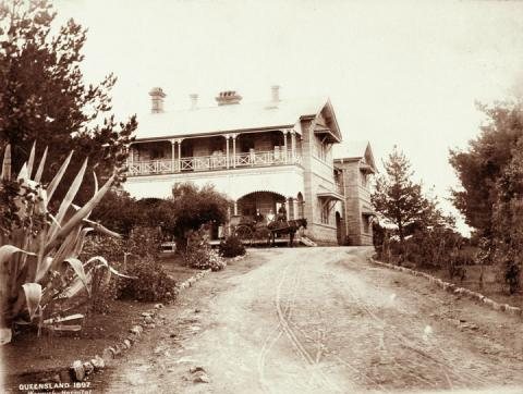 View of a garden and driveway leading up to a Queenslander-style building