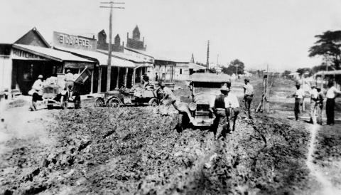 View of a dirt street congested with cars struggling to pass through the deep muddy holes