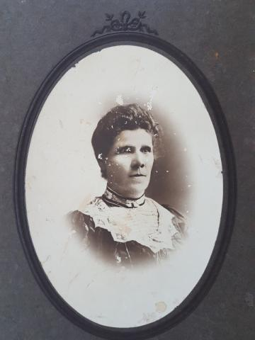 Black and white photograph of Elizabeth Campbell (nee Brydges). In this image Elizabeth is middle aged, and wears a dark dress with wide lace collar, and a small brooch at the neckline.
