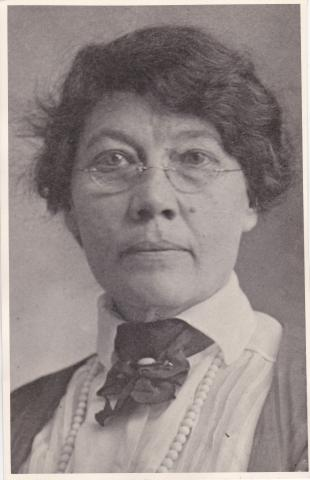 Black and white photograph of Mary Elizabeth Campbell, probably taken around 1919.  She is wearing small half-glasses, and a dark dress over white blouse with a ribbon rosette at the throat.  She also appears to be wearing a string of pearls.