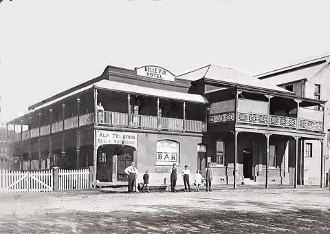 "Black and white photograph of the Belle Vue Hotel, Rockhampton.  The Hotel is a two-storey brick building with a large veranda around the upper storey, and a veranda along the lower storey.  A large sign above the Hotel proclaims its name, and a large sign on the end of the lower storey veranda says ""Alf Telford  Belle Vue Hotel"".  A large painted sign on the window facing the street says ""BAR"".   Alf Telford, the proprietor, and his family and employees stand proudly on the street in front."
