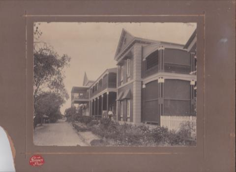 Black and white photograph of Rockhampton Hospital buildings, c.1910.  The two-storey buildings are brick and timber, with wide verandas upstairs and downstairs, surrounded by garden beds, with a gravel driveway., and white picket fencing