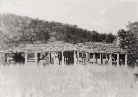 Black and white photograph of the ruins of the Rainbow Hotel.  The image shows a long, single-storey slab building in a state of decay, with large holes in the walls.  It is in the middle of a grassy paddock, with a hill in the background.
