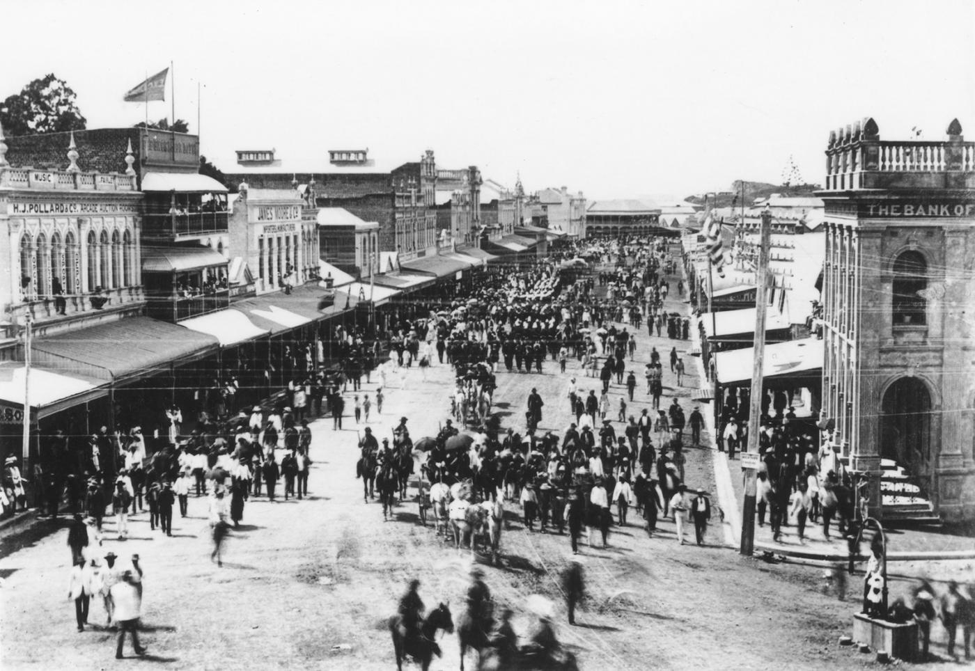 Crowded street scene showing hundreds of people gathered in the streets of Townsville for a procession