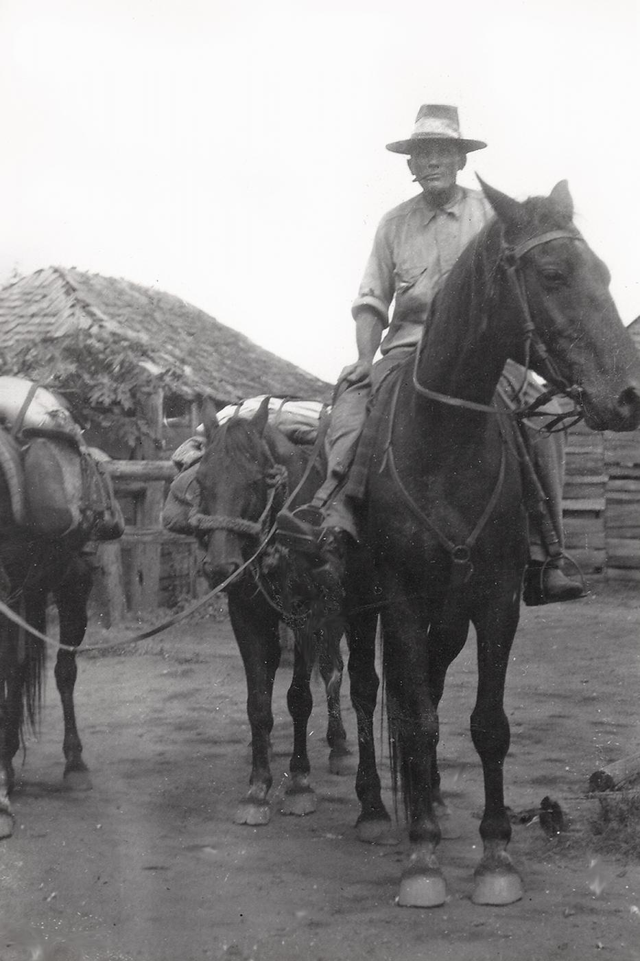 Black and White photograph of William Blair Campbell in the Kilburnie Saddling Yard with his bay horses.  He is riding one, and leading two packhorses loaded with gear.  He wears a wide-brimmed hat and work clothes, and is smoking a cigarette.