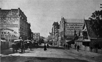 View of a historic Adelaide St, with cars and people walking