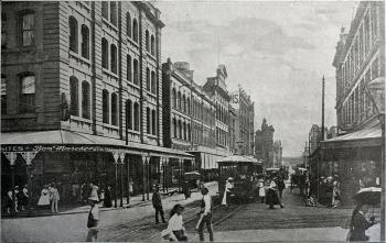 View of Adelaide Street showing people and cars down the main street