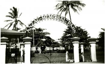 "View of a gate marking the entry to a large park, a sign on the gate reads ""Anzac Memorial Park"""