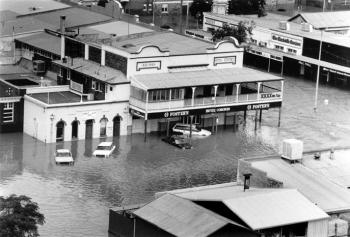 Aerial view of a flooded township, with the top story of a pub visible