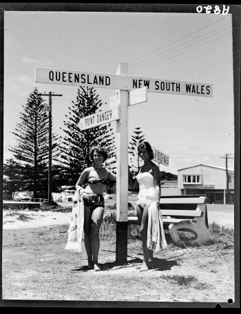Beach girls at Queensland and New South Wales border post, Coolangatta