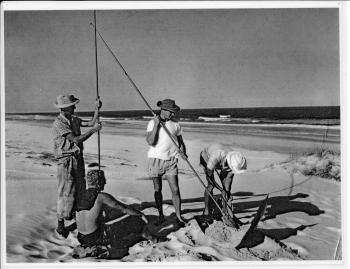 Group of four men working on an ocean beach. Two men are standing, one is sitting and one is bending over handling an implement. The one standing is holding a very long handled post-hole digger and the other standing man holds a long metal rod with the base obscured by the seated figure.