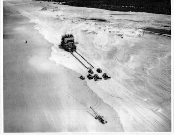 Moving a sandmining dredge along Main Beach on North Stradbroke Island, 1960s. Bulldozers are pulling the dredge, which is sliding on a constructed base.   Desc: Six bulldozers towing a mining dredge along a beach just above high tide mark. Beyond the sand dune is vegetation and an area of fresh water. The dunes are criss-crossed with tyre marks.