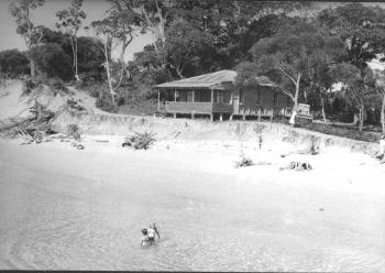 Black and white photograph of wooden cottage beside the beach at Amity Point.