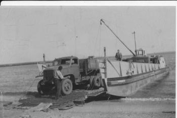 Sand trucks being unloaded from the barge onto the beach ca 1957