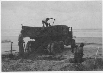 Three men shovelling mineral sand onto a truck on Main Beach, North Stradbroke Island. The North Stradbroke Island sandmining industry started soon after World War 2 (1939-1945). It began on the east-facing Main Beach where wave action exposed seams of the black, mineral-bearing sand.