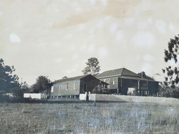 Black and white photograph of Kilburnie Homestead, taken approx 1950.   There is a single-storey detached kitchen and storeroom on the left, and the larger two-storey living areas of the homestead on the right.  A white picket fence and trees surround the structures.
